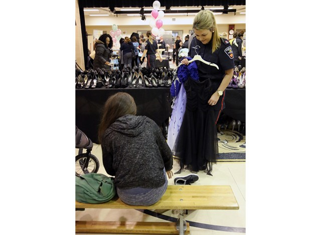 A police officer holding a dress while a girl tries on shoes