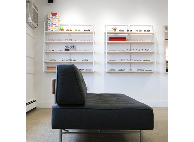 A sunglasses shop with grey couch with displays of glasses in the background