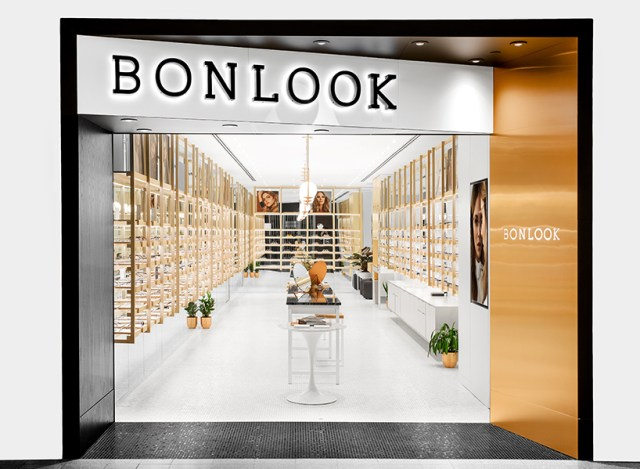 A sunglasses shop with a black BonLook sign and a modern interior with wood, white and foliage