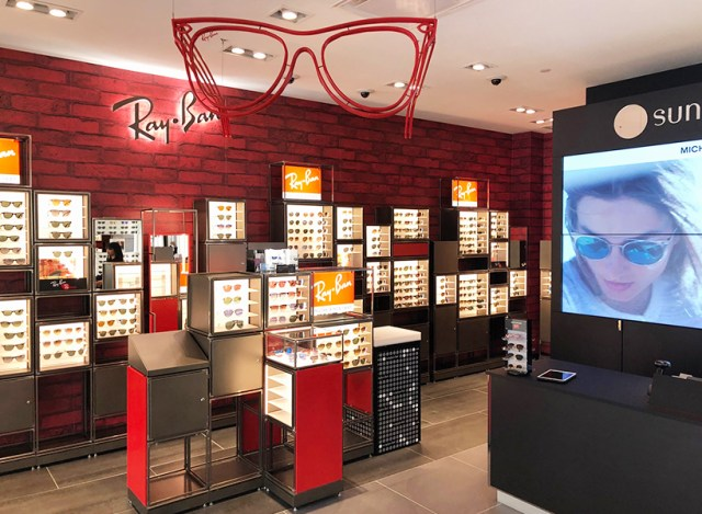 A sunglasses shop with a sleek red and black interior, a Ray Ban sign and displays of colourful sunglasses
