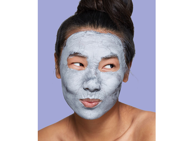 A woman wearing a clay face mask