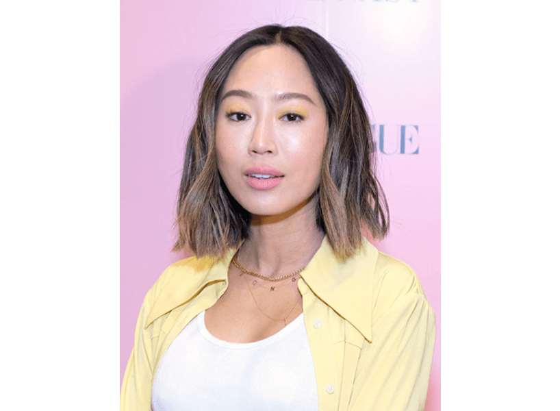 2020 hair trends: Aimee Song against a pink background with a textured bob cut, including caramel blonde highlights!