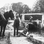 black and white photo of a man with horse in front of Flatford Lock