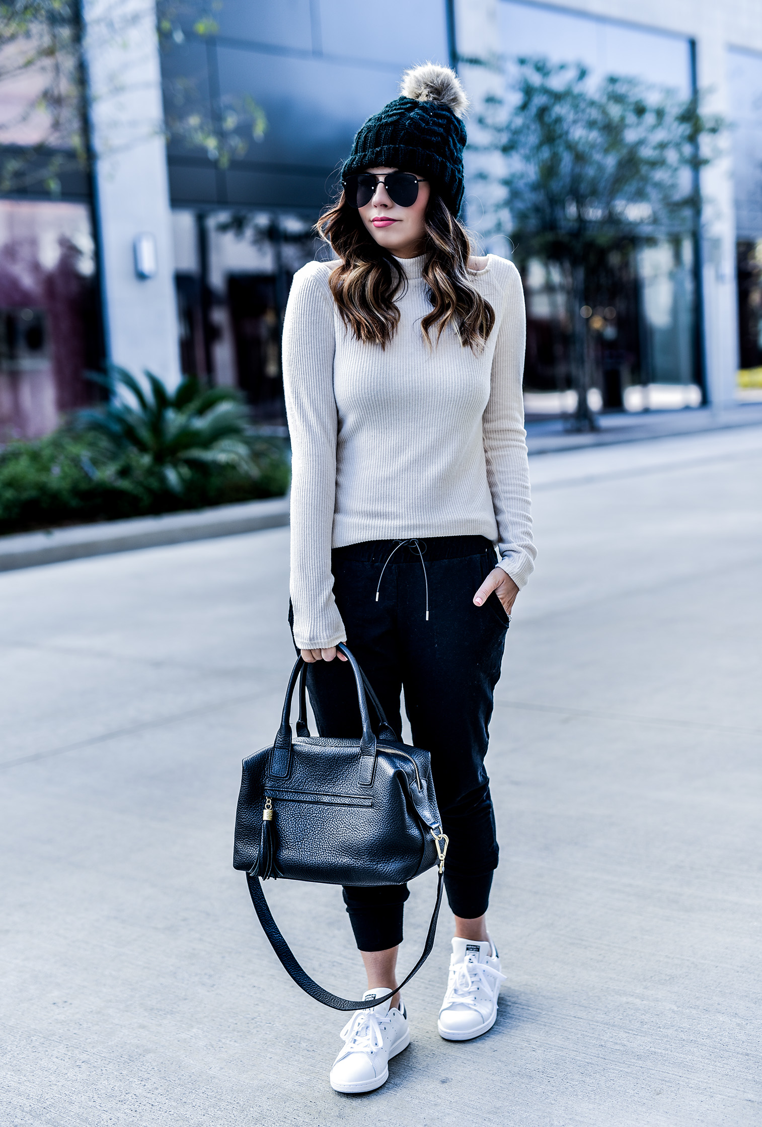 Fashion and lifestyle blogger Tiffany Jais wearing free people skinny black joggers, Stan Smith sneakers, a white cutout sweater by Revolve, and a faux fur pom pom beanie | streetstyle fashion, women's fashion