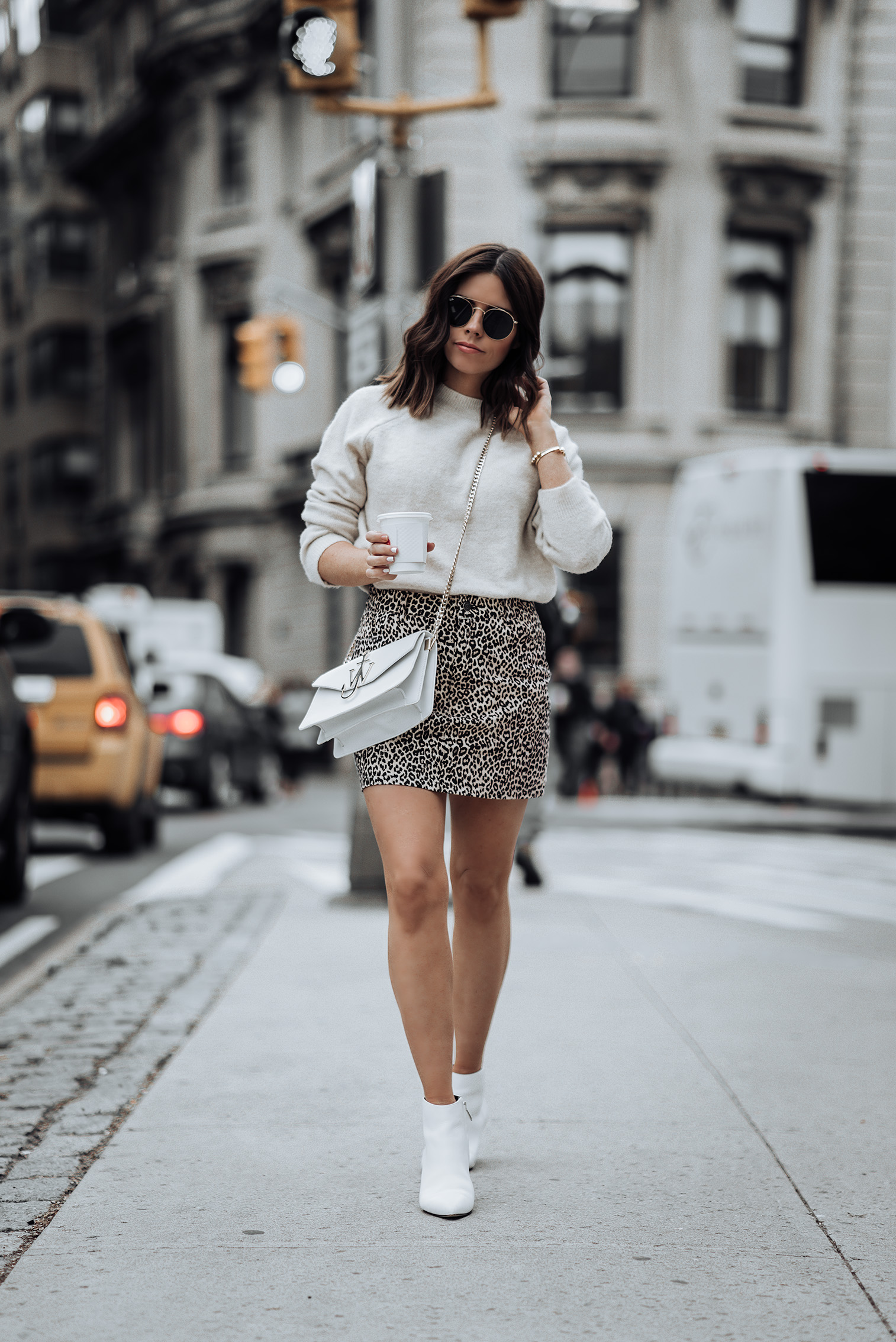 Revolve Leopard Mini Skirt | Sand color Sweater | J.W. Anderson Logo Purse | Similar white Ankle Boots here | #liketkit #ootd #style #blog #leopardskirt #streetstyle