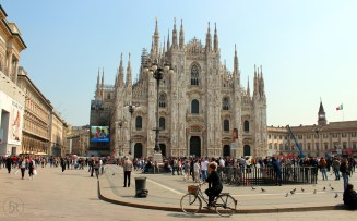 Crowded place in front of Milan Cathedral with a cyclist also enjoying the nice weather
