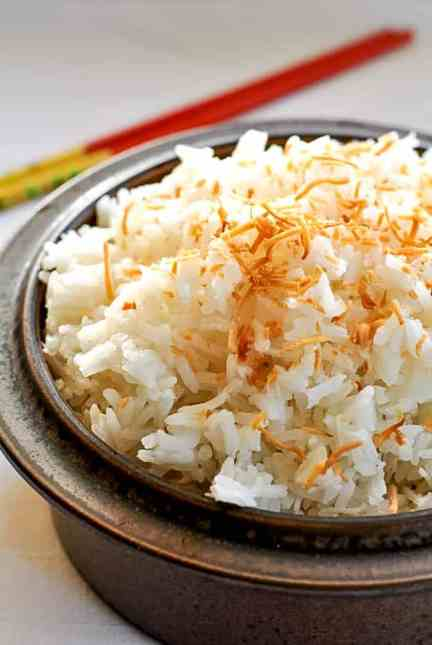 Thai Coconut Rice in a brown stoneware bowl with chopsticks.