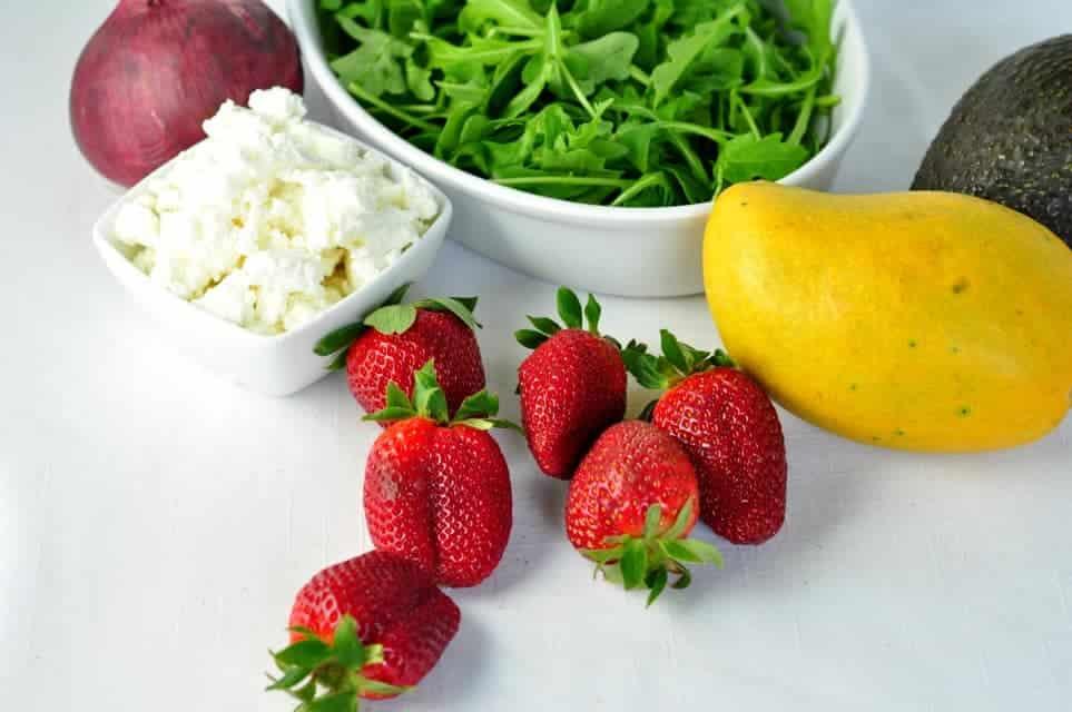 Ingredients for strawberry mango salad. Arugula, red onion, goat cheese, strawberries, mango and avocado