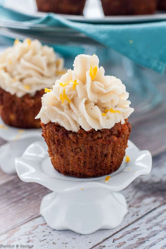 Paleo Carrot Cake Cupcakes with Coconut Butter Frosting on a pedestal stand