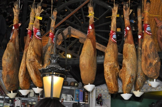 Iberico ham hanging from ceiling in a tapas bar in Seville