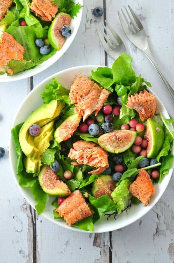 Grill salmon, arrange some greens, figs, berries and avocado, top with chunks of salmon and drizzle it all with a tasty honey-balsamic vinaigrette. Spring or summertime meal in a bowl! #grilledsalmon #salad #figs #blueberries #honeybalsamic #summersalad #avocado