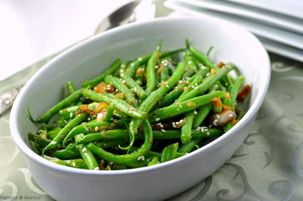 Sesame Ginger Green Beans sprinkled with sesame seeds in a white bowl.