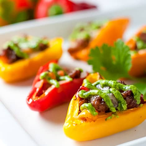 Taco Stuffed Mini Peppers. These easy appetizers make a kid-friendly snack too. Stuffed with taco-seasoned meat and topped with avocado cream.