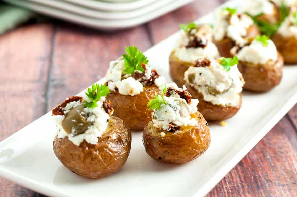Easy 3-ingredient Stuffed Mini Potatoes lined up on a white serving tray.