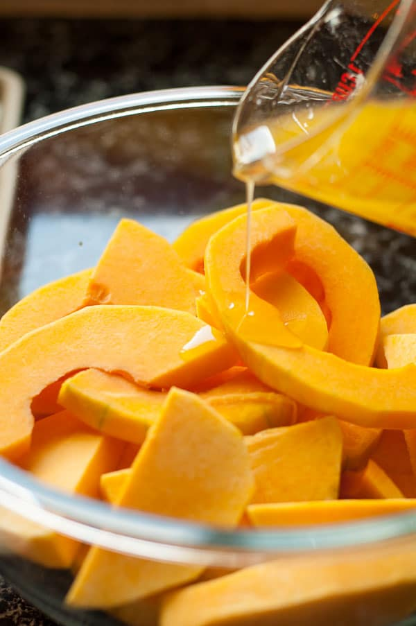Pouring glaze on to a bowl of Butternut Squash with Fresh Rosemary and Honey-Lime Glaze |www.flavourandsavour.com