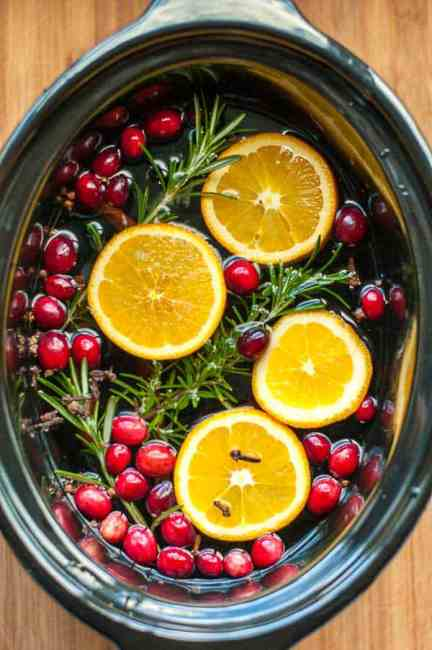 Simmering holiday potpourri in a slow cooker with cinnamon sticks, orange slices, cloves, allspice and star anise.