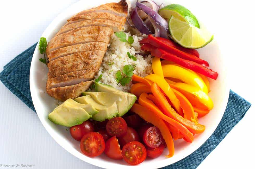 Chicken Fajita Bowl with Cauliflower Rice is a paleo meal-in-a-bowl! Succulent fajita chicken, with colourful peppers, tomatoes, avocado and cilantro-lime cauliflower rice, all in one super bowl, makes a tasty Tex-Mex dinner.