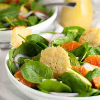 Orange and Avocado Salad with Parmesan Crisps. Sweet Cara Cara oranges, creamy avocados, fennel and red onion on a bed of fresh greens, garnished with crunch Parmesan crisps.