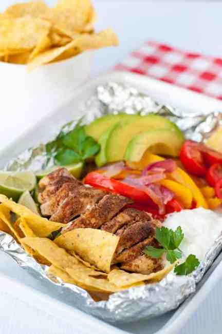Easy Chicken Fajitas in Foil Packets made with taco-seasoned chicken, peppers, avocado, tomatoes, sour cream and tortilla chips on a checkered cloth.