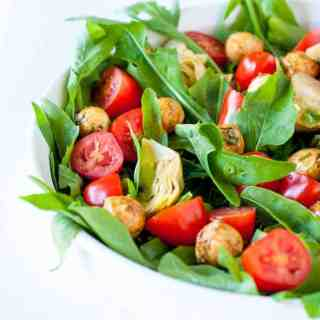 Balsamic Bocconcini Cherry Tomato Salad with Marinated Artichokes and Arugula. This vegetarian salad packs a punch of flavour. Peppery arugula , balsamic bocconcini balls , marinated artichokes and fresh cherry tomatoes combine to make a salad I could eat every day! |www.flavourandsavour.com