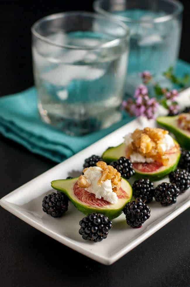 Fresh Figs with Goat Cheese and Maple Walnuts on a rectangular white plate with blackberries