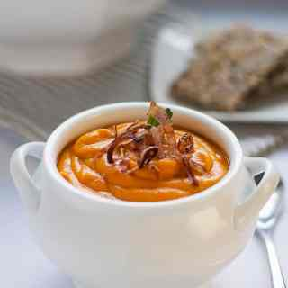 Slow Cooker Sweet Potato Turmeric Soup in a white soup bowl garnished with crispy fried shallots.
