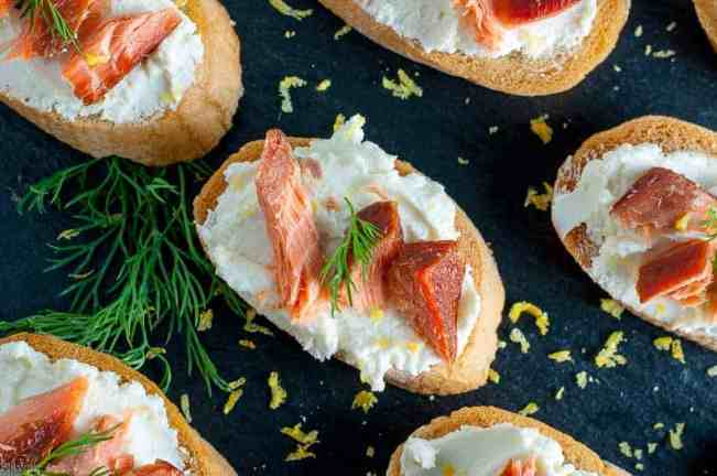 Smoked Salmon Crostini with Whipped Honey Lemon Goat Cheese on a black background