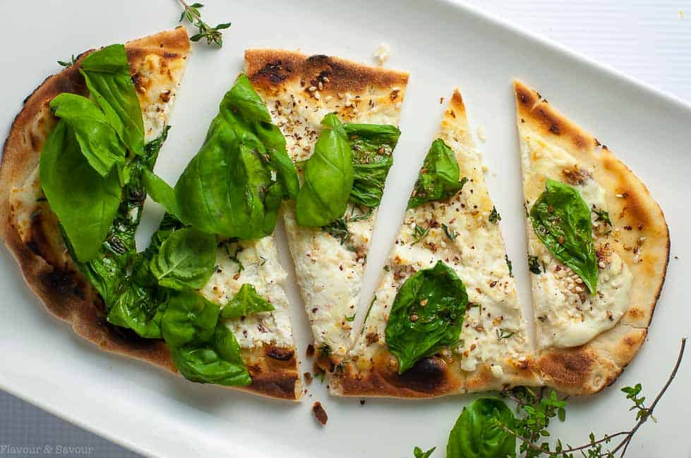 Whipped Goat Cheese Sesame Flatbread with Za'atar garnished with fresh basil and cut into wedges.