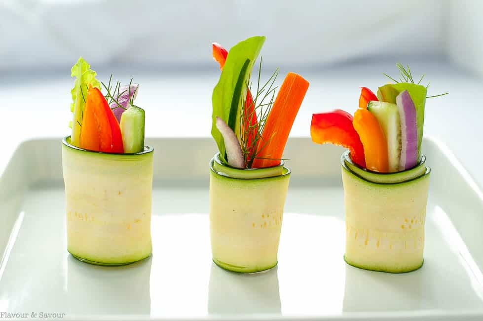 Fresh Zucchini Roll-ups with raw colourful vegetables on a white tray