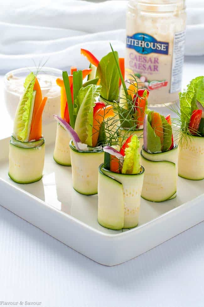 Fresh Veggie Zucchini Roll-Ups on a serving tray with Litehouse Caesar dressing as a dip.