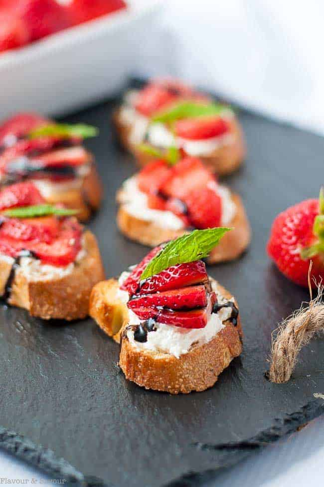Add a mint leaf to garnish Strawberry Whipped Feta Crostini with Balsamic Drizzle |www.flavourandsavour.com