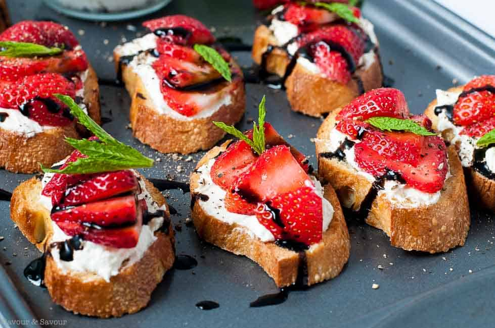 Strawberry Whipped Feta Crostini with Balsamic Drizzle on a baking sheet  |www.flavourandsavour.com