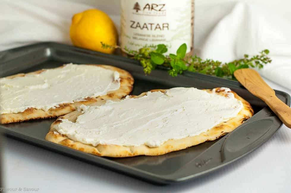Prepare Whipped Goat Cheese Flatbread with Za'atar by spreading goat cheese mixture, then heating it under the broiler.