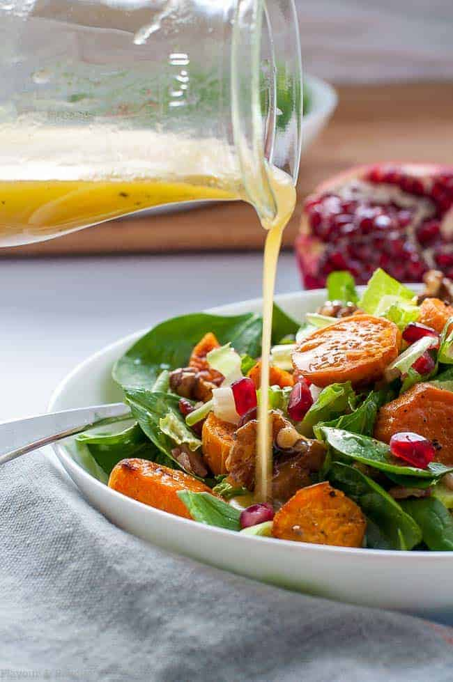 Pouring Dressing on Roasted Sweet Potato Spinach Salad with Maple Walnuts and Bacon