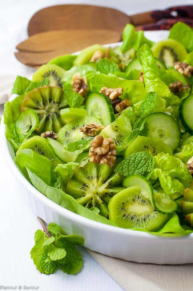 Kiwi Cucumber Salad with Walnuts and Fresh Mint shown in a shallow bowl with salad servers.