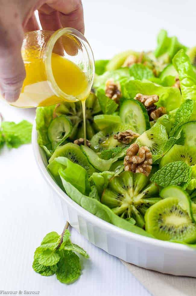 Drizzling dressing on Kiwi Cucumber Salad with Walnuts and Fresh Mint