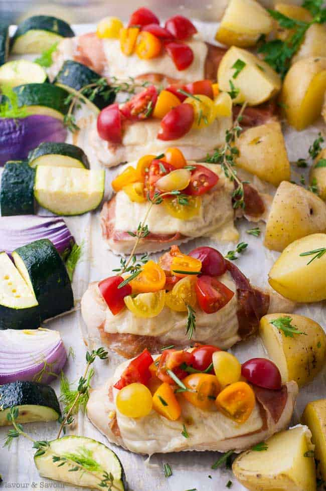 Prosciutto and Cheesy Chicken Sheet Pan Dinner topped with cherry tomatoes and herbs.