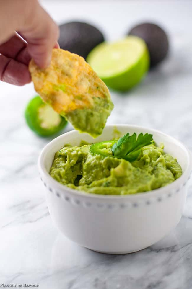 Dipping a chip into Jalapeño guacamole made to spread on Chipotle Peach Shrimp Tostadas