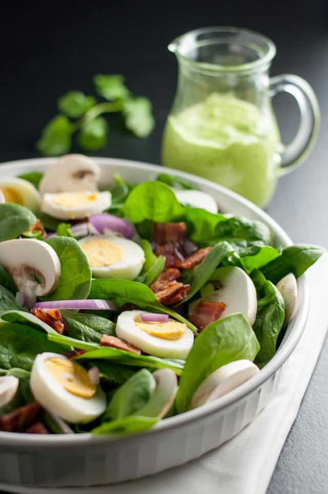 Classic Spinach Salad with Creamy Avocado Dressing with hard boiled eggs and bacon.