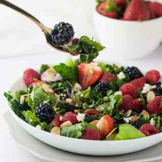 A forkful of Triple Berry Mixed Green Salad with strawberries, blackberries, raspberries, feta cheese and flaked toasted almonds.