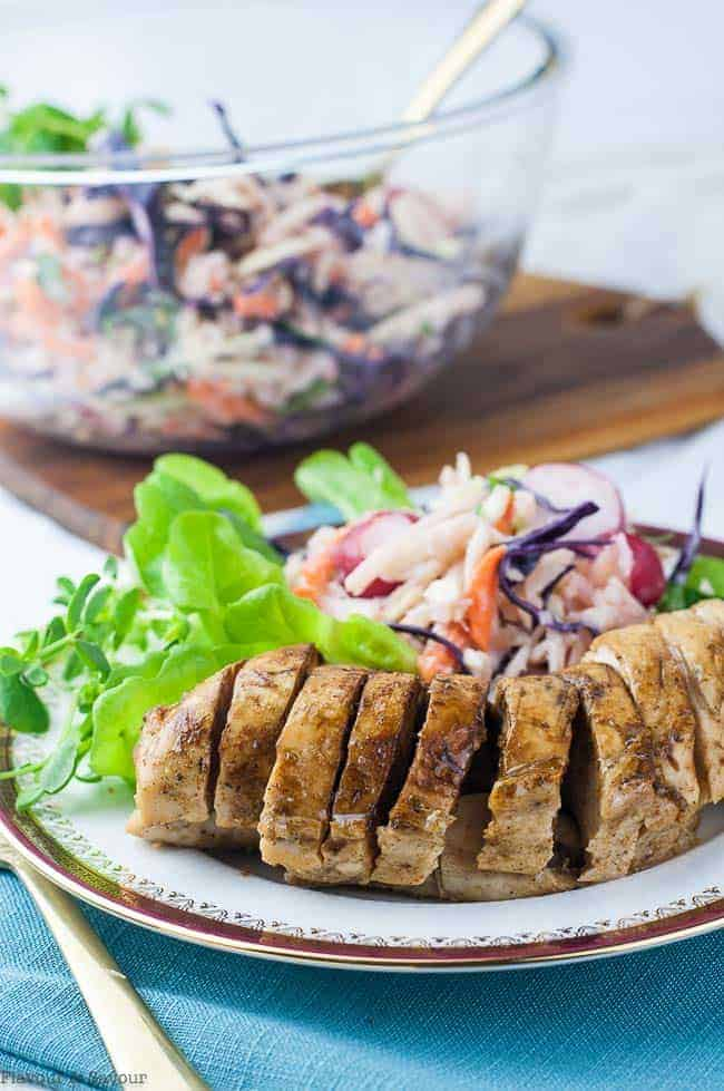 Instant Pot Caribbean Jerk Chicken Breasts sliced on a plate with coleslaw.