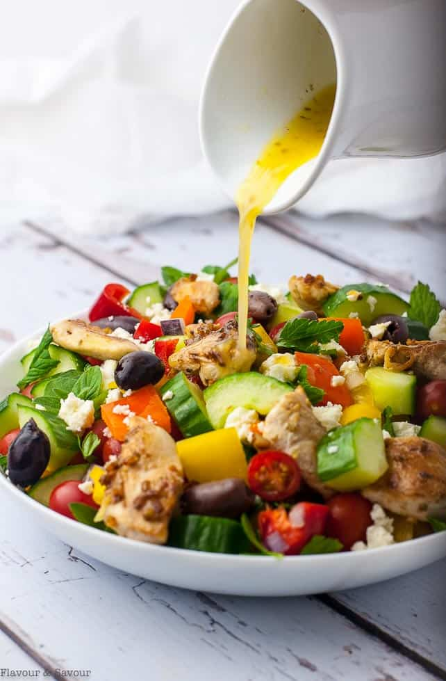Pouring dressing on Marinated Lemon Chicken Greek Salad with Mint