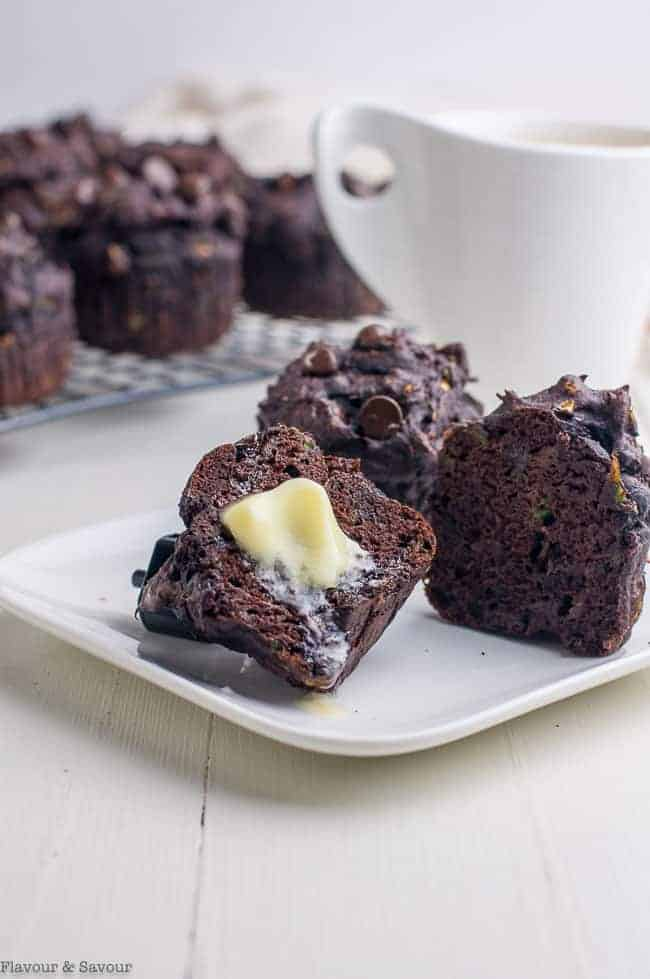 Gluten-Free Double Chocolate Zucchini Muffins with melted butter and a cup of coffee.