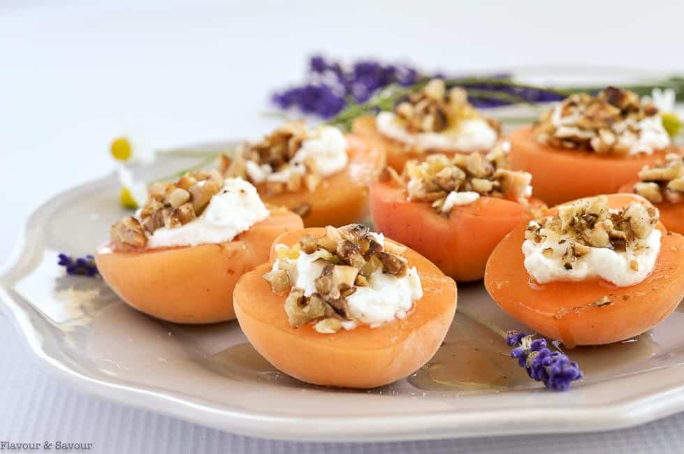 Close up view of a finger food appetizer of fresh apricot halves stuffed with goat cheese, toasted walnuts and lavender-infused honey