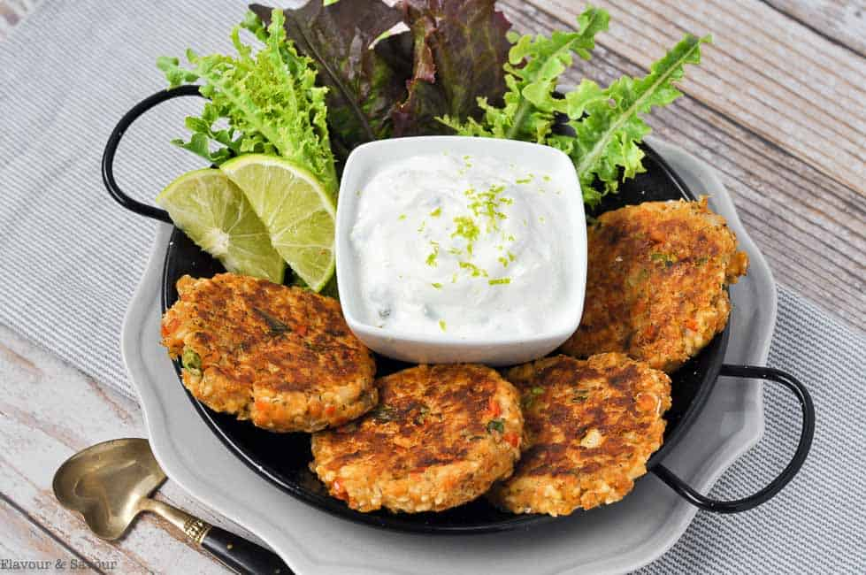 four salmon patties on a plate with lime slices and dip