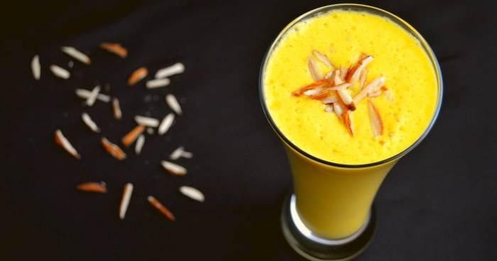 lassi in a glass with a almond slices on black table