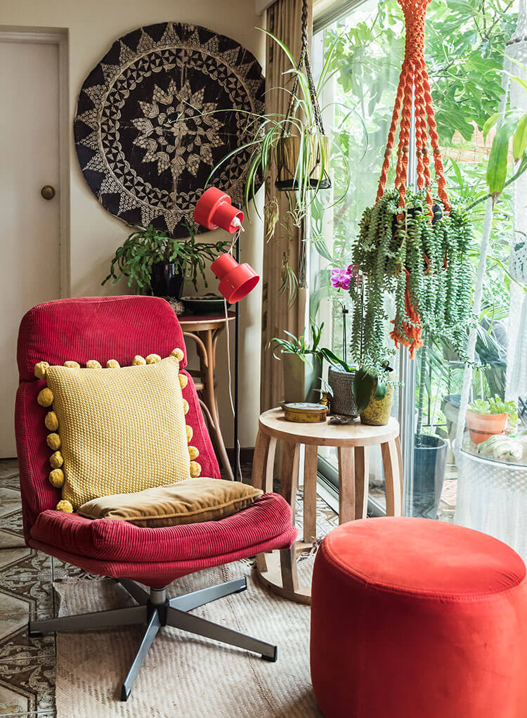 The interior of a vintage-inspired home featuring a chair with a red facade, hanging plant, and an intricate tapestry that all steal the show.