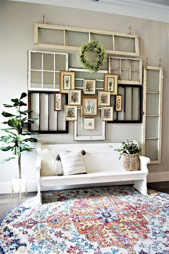 Vintage flower prints are layered over vintage windows for a vintage-inspired entryway.