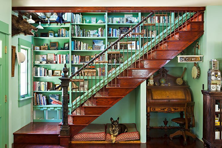 A rustic renovation featuring a wooden, open staircase with a dog resting beneath it.