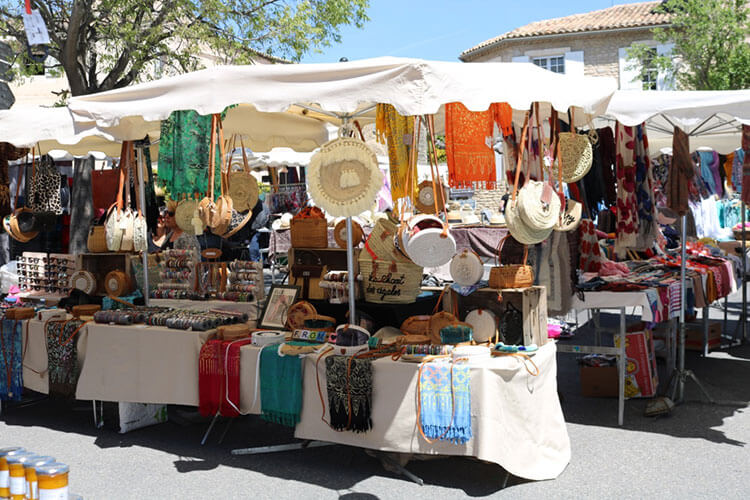Vendor stand with a white awning and several pieces of antique clothing for sale.